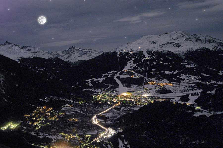 La bellezza del panorama di Bormio in una notte di luna piena}